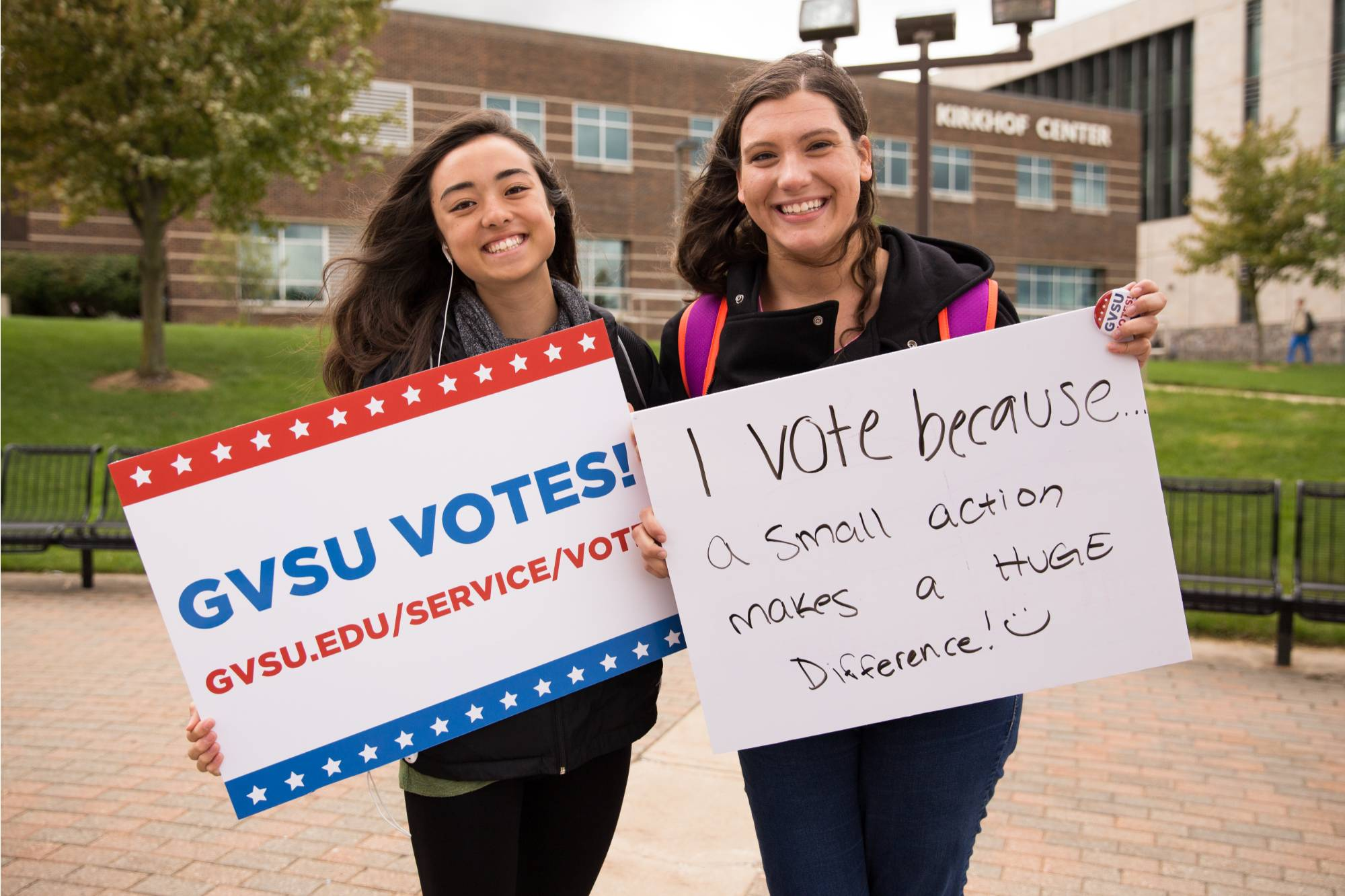 Two girls holding up GVSU votes signs